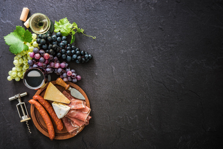 table top: Wineglasses with grapes, cheese, ham and corks on dark background with copy space