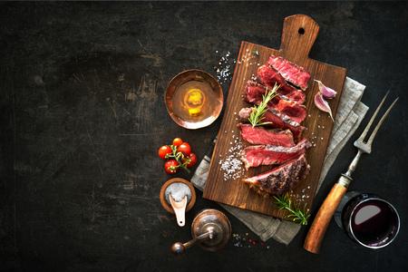 Sliced medium rare grilled beef ribeye steak on cutting board on dark background