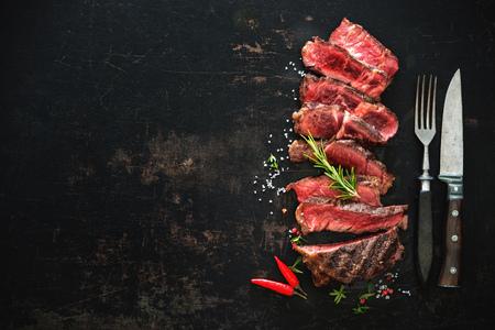 Gesneden medium, zeldzame, geroosterde Biefstuk Ribeye Biefstuk op donkere achtergrond