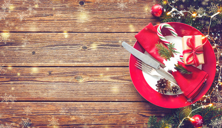 Christmas table setting with fir tree and lights on a wooden table