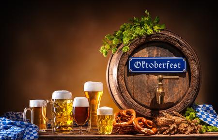 octoberfest: Oktoberfest barril de cerveza y vasos de cerveza con trigo y saltos en la mesa de madera