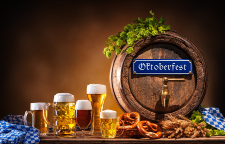 Oktoberfest beer barrel and beer glasses with wheat and hops on wooden table 免版税图像