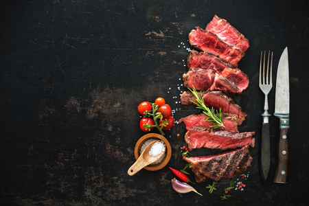 Sliced medium rare grilled beef ribeye steak on dark background