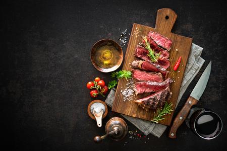 어두운 배경에 커팅 보드에 중간 희귀 구이 쇠고기 ribeye 스테이크를 슬라이스