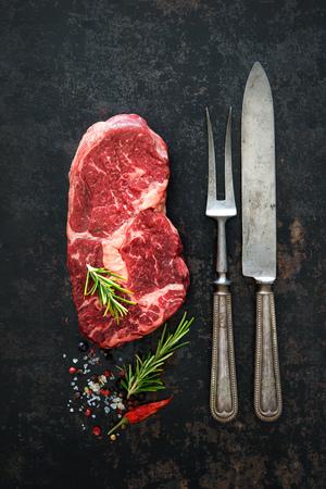 cutting: Raw dry aged beef ribeye steak on dark background