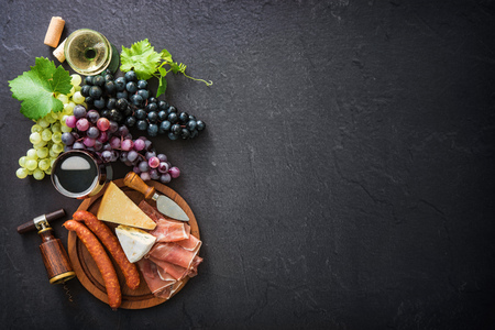 Wineglasses with grapes, cheese, ham and corks on dark background with copy space