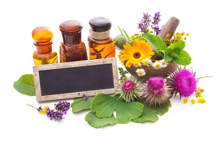 Tincture bottles and healing herbs in mortar isolated on white. Herbal medicine. Medicinal plants Stockfoto