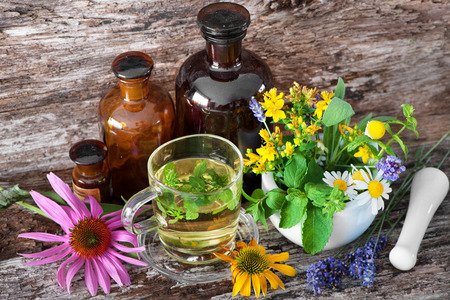 Cup of herbal tea with tincture bottles and healing herbs in mortar on wooden table. Herbal medicine. Medicinal plants