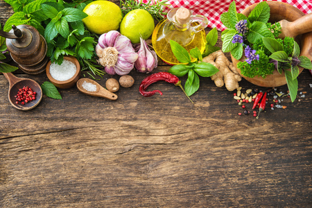 board: Fresh herbs and spices on wooden table. Top view with copy space