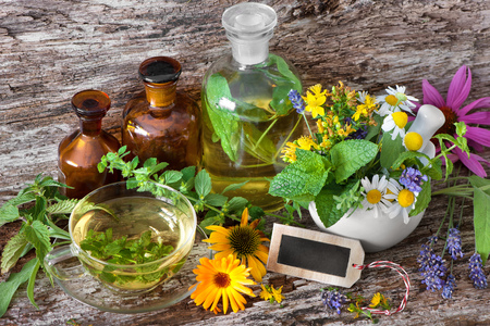 healer: Cup of herbal tea with tincture bottles and healing herbs in mortar on wooden table. Herbal medicine. Medicinal plants
