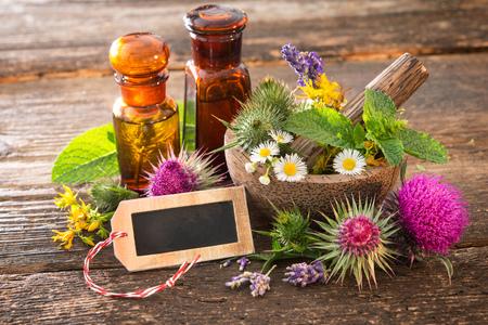 elixir: Botellas de tintura y hierbas curativas en mortero en mesa de madera. Medicina herbaria. Plantas medicinales