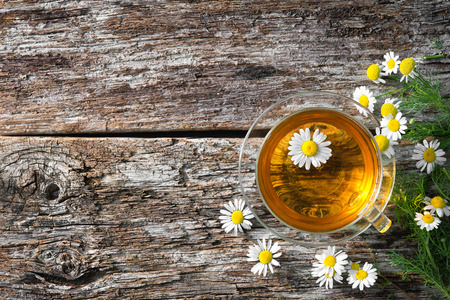 Cup of medicinal chamomile tea on wooden Stock Photo