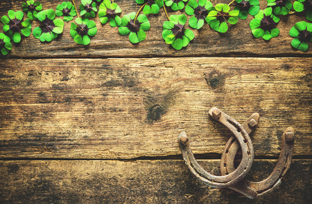 St. Patricks day, lucky charms. Horseshoe and shamrock on wooden background Imagens