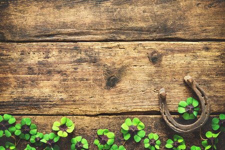 St. Patricks day, lucky charms. Horseshoe and shamrock on wooden background Stock fotó