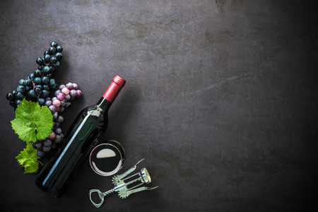 Bottle of red wine, wineglass, grapes and corks on dark background