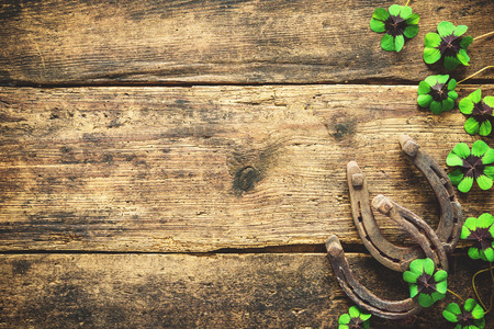 St. Patrick's day, lucky charms. Horseshoe and shamrock on wooden background