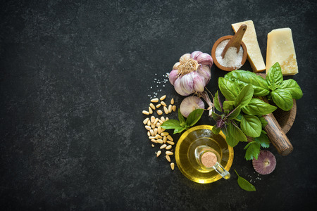 raw: Ingredients for homemade green basil pesto on black stone table. Parmesan cheese, basil leaves, pine nuts, olive oil, garlic, salt and pepper Stock Photo