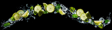 Lime and lemon pieces with mint and ice in water splash Reklamní fotografie