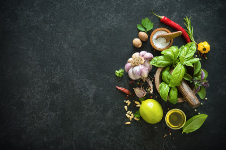 table top: Herbs and spices on black stone table. Ingredients for cooking. Top view with copy space Stock Photo
