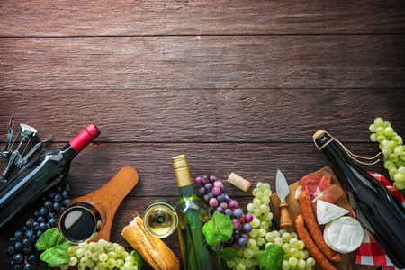 Wine bottles with grapes, cheese, ham and corks on wooden background with copy space Stock Photo