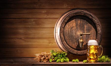 Oktoberfest biervat en bierglas met tarwe en hop op houten tafel
