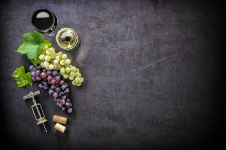 vintage background: Wineglasses with grapes and corks on dark background with copy space Stock Photo