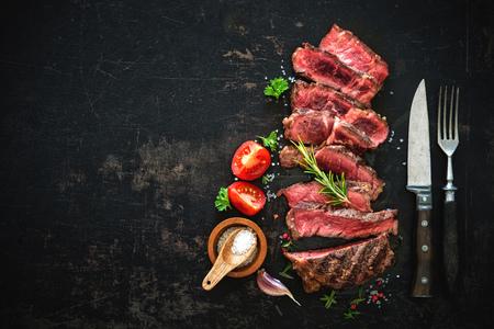 cutting: Sliced medium rare grilled beef ribeye steak on dark background