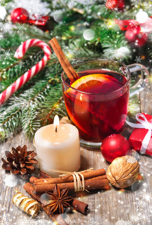 Red mulled wine hot drink with cinnamon stick, slices of orange and spices, on holiday decorated Christmas table Stock Photo