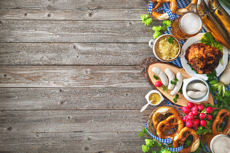 Oktoberfest beer, pretzels and various Bavarian specialties on wooden background Stock Photo