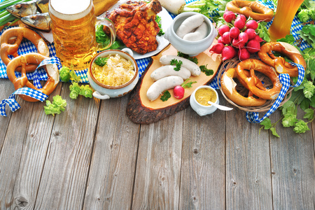 Oktoberfest beer, pretzels and various Bavarian specialties on wooden background Фото со стока