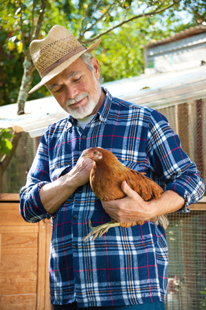 Happy organic farmer holds chicken in his arms in front of hen house Stock Photo