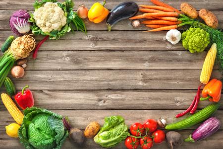 木製の背景に新鮮な野菜のフレーム