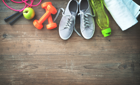Fitness equipment, healthy food, sneakers, water bottle and towel on wooden floor. Top view