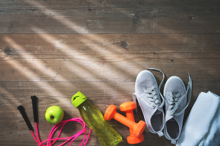 Fitness equipment, healthy food, sneakers, water bottle and towel on wooden floor.  Top view Stock Photo