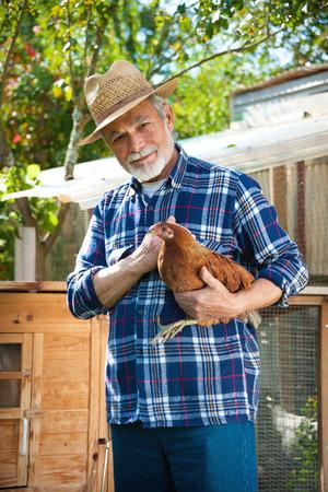 幸せな有機農家鶏小屋の前に彼の腕で鶏を保持します。