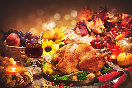 Roasted whole turkey on festive rustic table with autumn decoration for Thanksgiving Day