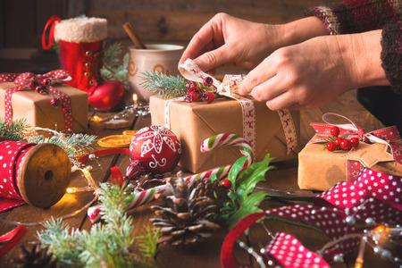 Die weiblichen Hände, die handgemachte Geschenke des Weihnachtsfeiertags einwickeln, im Kraftpapier mit Band auf Holztisch. Draufsicht