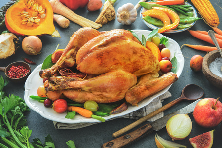 Roasted whole turkey with cooking ingredients on kitchen table. Thanksgiving or Christmas cooking