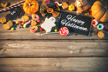 Sweets for Halloween and fresh pumpkin on wooden table with copy space. Trick or treat