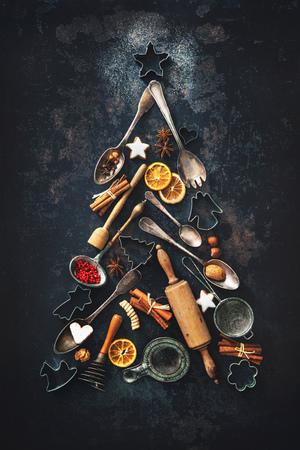 Kerstmis bakken achtergrond met fir tree gemaakt van keukengerei, koekjes, kruiden, kaneelstokjes, anijs sterren op rustieke bakplaat, bovenaanzicht