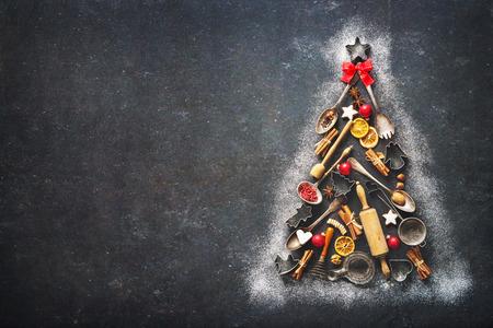 Fond de cuisson de Noël avec sapin fabriqué à partir d'ustensiles de cuisine, biscuits, épices, bâtons de cannelle, étoiles d'anis sur la plaque de cuisson rustique, vue de dessus