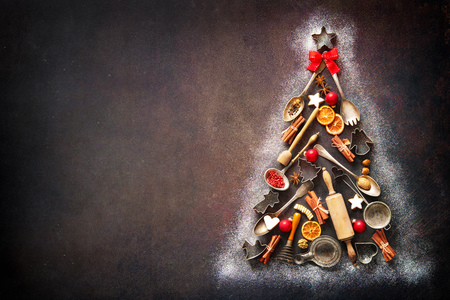 Christmas baking background with fir tree made from kitchen utensils, cookies, spices, cinnamon sticks, anise stars on rustic baking tray, top view