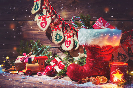Christmas background. Advent calendar and Santa's shoe with gifts on rustic wooden background