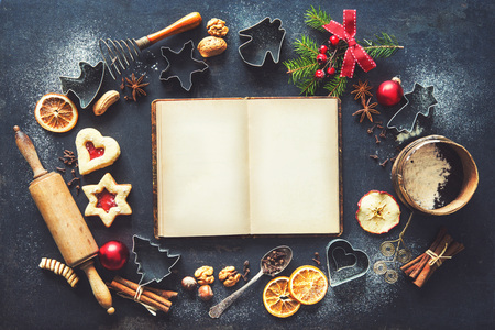 Christmas baking sweet food frame with recipes book, homemade cookies, spices, kitchen utensils, fir branches and red holiday decoration on dark rustic baking tray. Top view Banco de Imagens