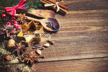 Christmas background with baking utensils, spices, anise stars, fir branches and  holiday decoration on dark rustic wooden table Standard-Bild