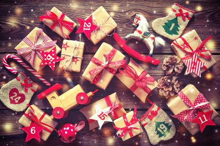 Boże Narodzenie w tle. Zapakowane w pudełka upominkowe wstążki, zabawki i inne prezenty z numerami jako Kalendarz adwentowy na tle rustykalnym drewnianym stole Zdjęcie Seryjne