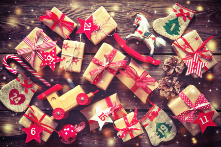 Christmas background. Wrapped with ribbon gift boxes, toys and others presents with the numbers as Advent calendar on rustic wooden table background