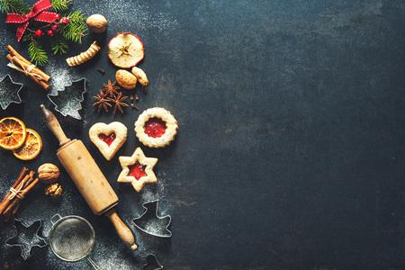 Boże Narodzenie pieczenia słodkiego tła z domowych ciasteczek, przypraw, przyborów kuchennych, gałęzi jodłowych i czerwonej dekoracji świątecznej na ciemnej rustykalnej blasze do pieczenia. Widok z góry
