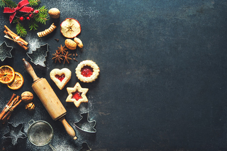 Christmas baking sweet food background with homemade cookies, spices, kitchen utensils, fir branches and red holiday decoration on dark rustic baking tray. Top view