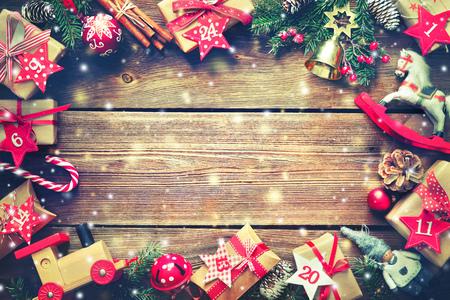 Kerst achtergrond. Frame van verpakte geschenkdozen, speelgoed en anderen presenteert met de nummers als adventskalender op rustieke houten tafel achtergrond